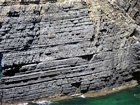 The Ross Formation of Loop Head is here expressed as turbidite sheet sands that accumulated as deepwater fan lobes that were dissected by sparse shallowly incised channels. As Elliot (2000) records these are the thicker bedded, high net-to-gross, sheet turbidites of the lower part of the Ross Sandstone Formation turbidite system. The height of these cliffs is between 45-50 m. Note the shaley partings that may compartmentalize these sands and seperate them in terms of their reservoir quality from those above. Shallow though the channeling may be it may enhance vertical reservoir continuity between the stacked sheets