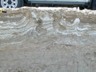 Note anhydrite layer and nodules (white-grey material that looks like cream cheese) in a matrix of storm washover and outwash (light brown sediment). This layer just above the marine water table and below the surface halite crusts. Note the vertical tubes (filled with the darker sediment) penetrating the anhydrite nodules and layers. These tubes have smooth curvillinar walls that appear to have been produced by small insects. Note the intertidal to just subtidal lagoonal muds and sands below the anhydrite layers. Musafa Channel Section Abu Dhabi